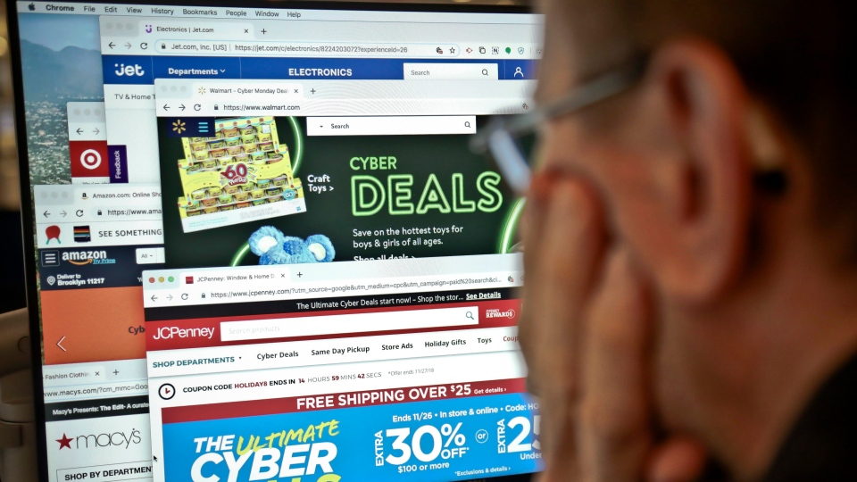 A journalist looks at a computer screen with webpages arranged to show Cyber Monday deals by various online retailers Monday Nov. 26, 2018, in New York. (AP Photo/Bebeto Matthews)