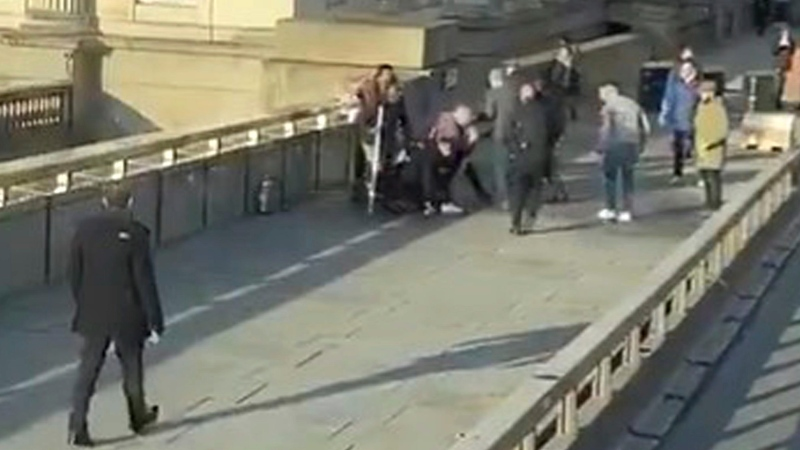 In this grab taken from video made available by @HLOBlog, a man is surrounded by members of the public before armed police arrived during an incident on London Bridge, in London, Friday, Nov. 29, 2019. (@HLOBlog via AP)