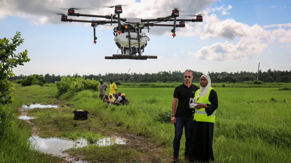 In this photo taken Thursday, Oct. 31, 2019, Eduardo Rodriguez, left, of drone manufacturer DJI, trains Khadija Ali Abdulla, right, from the State University of Zanzibar, how to fly a drone to spray the breeding grounds of malaria-carrying mosquitoes, at Cheju paddy farms in the southern Cheju region of the island of Zanzibar, Tanzania. (AP Photo/Haroub Hussein)