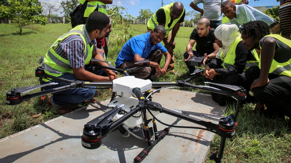 n this photo taken Thursday, Oct. 31, 2019, Eduardo Rodriguez, center-right, of drone manufacturer DJI, shows trainee drone pilots from the State University of Zanzibar how to fly a drone to spray the breeding grounds of malaria-carrying mosquitoes, at Cheju paddy farms in the southern Cheju region of the island of Zanzibar, Tanzania. (AP Photo/Haroub Hussein)