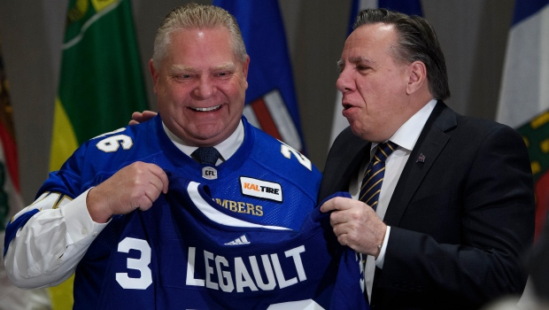 Doug Ford, left, Premier of Ontario, gives a Maple Leafs jersey to Francois Legault, Premier of Quebec, during a meeting of the Council of the Federation which comprises all 13 provincial and territorial Premiers in Mississauga, Ont., on Monday, December 2, 2019. THE CANADIAN PRESS/Nathan Denette