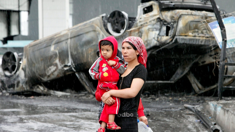 In this Wednesday, July 15, 2009, file photo, a Uighur woman and a child walk past a burned car at a destroyed dealership in the Uighur section following riots in Urumqi, western China's Xinjiang province. (AP Photo/Eugene Hoshiko, File)