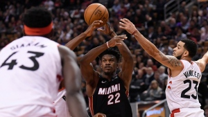 Miami Heat forward Jimmy Butler (22) passes the ball while under pressure from Toronto Raptors guard Fred VanVleet (23) as Raptors' Pascal Siakam (43) looks on during second half NBA action in Toronto on Tuesday, Dec.3, 2019. THE CANADIAN PRESS/Nathan Denette