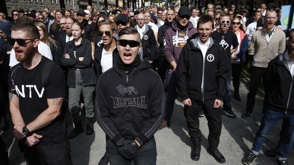 Supporters of the neo-Nazi Nordic Resistance Movement chant slogans during a demonstration at the Kungsholmstorg square in Stockholm, Sweden, Saturday, Aug. 25, 2018. (Fredrik Persson/TT News Agency via AP)