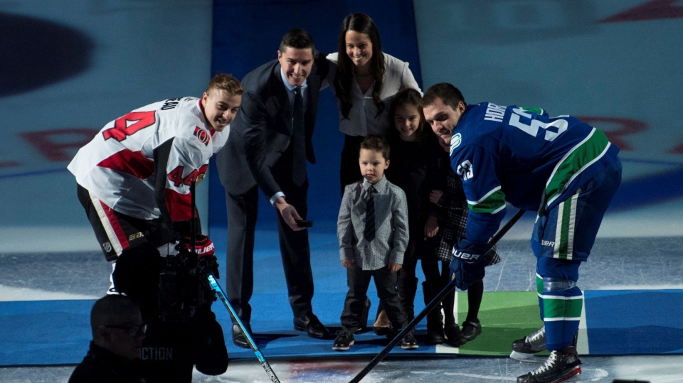 Former Vancouver Canucks player Alex Burrows takes part in a ceremonial puck drop with Vancouver Canucks centre Bo Horvat (53) and Ottawa Senators centreJean-Gabriel Pageau (44) prior to the first period in Vancouver, Tuesday, December 3, 2019. Burrows was inducted into the Vancouver Canucks Ring of Honour. THE CANADIAN PRESS/Jonathan Hayward