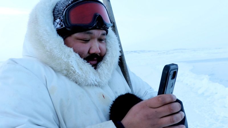 Puasi Ippak tests out the Siku mobile app in a handout photo. A social media app geared towards the outdoor lives of Inuit launched Wednesday with features that tie traditional knowledge to smart phone technology. THE CANADIAN PRESS/HO-Arctic Eider Society