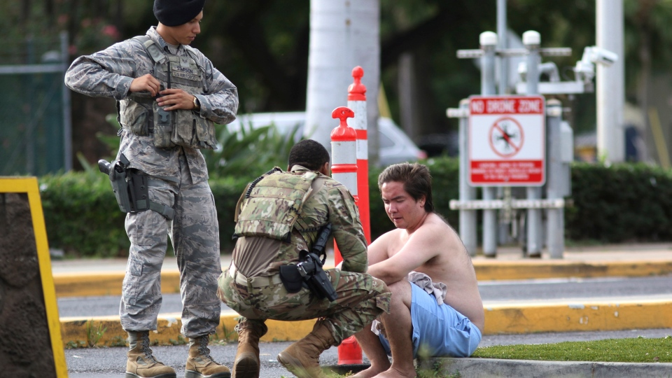 Security forces attend to an unidentified male outside the the main gate at Joint Base Pearl Harbor-Hickam, Wednesday, Dec. 4, 2019, in Hawaii, following a shooting. (AP Photo/Caleb Jones)