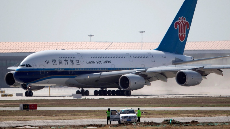 Airport crew watch from their car as a China Southern Airlines passenger jet lands during the first test flight of the new Beijing Daxing International Airport on Monday, May 13, 2019.  (AP Photo/Ng Han Guan)