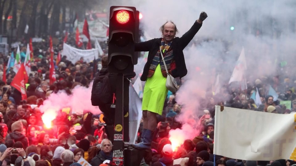A man stands on a traffic light during a demonstration in Paris, Thursday, Dec. 5, 2019. (AP Photo/Thibault Camus)