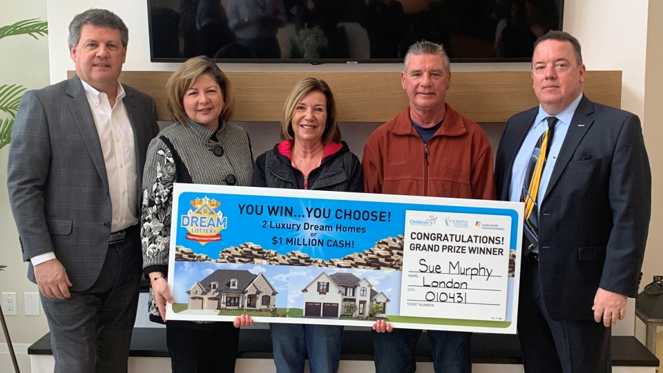Officials pose with Dream Home Lottery winners