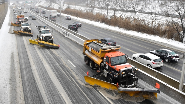A line of snow plows clears the Gardiner Expressway in Toronto on Tuesday, Feb.12, 2019. THE CANADIAN PRESS/Frank Gunn
