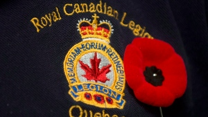 A poppy is pinned next to a Royal Canadian Legion crest in Montreal, November 2, 2012. The Royal Canadian Legion is set to call on the Harper government to take better care of wounded veterans and their families. THE CANADIAN PRESS/Graham Hughes.