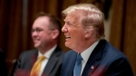 U.S. President Donald Trump, right, accompanied by acting Chief of Staff Mick Mulvaney, left, smiles at a luncheon with members of the United Nations Security Council in the Cabinet Room at the White House in Washington, Thursday, Dec. 5, 2019. (AP Photo/Andrew Harnik)
