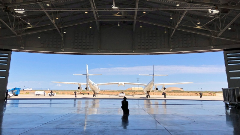 In this Aug. 15, 2019 file photo, Virgin Galactic ground crew guide the company's carrier plane into the hangar at Spaceport America following a test flight over the desert near Upham, New Mexico. (AP Photo/Susan Montoya Bryan)