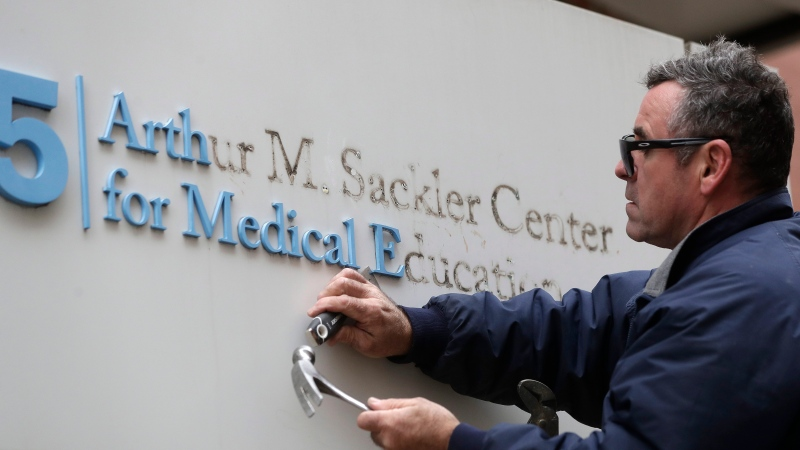 Worker Gabe Ryan removes a sign that includes the name Arthur M. Sackler at an entrance to Tufts School of Medicine, Thursday, Dec. 5, 2019, in Boston. (AP Photo/Steven Senne)