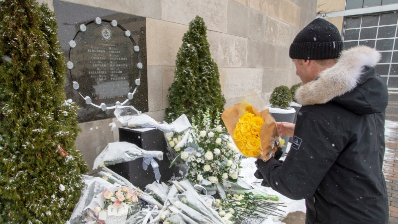 Former student Richard Grégoire places fourteen roses at the school's memorial to mark the 30th anniversary of the 1989 École Polytechnique attack where a lone gunman killed 14 female students Friday, December 6, 2019 in Montreal.THE CANADIAN PRESS/Ryan Remiorz