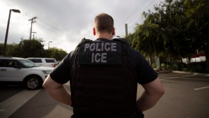 In this July 8, 2019, photo, a U.S. Immigration and Customs Enforcement (ICE) officer looks on during an operation in Escondido, Calif. (AP Photo/Gregory Bull)
