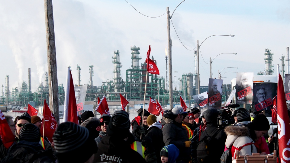 The Co-op Refinery Complex is seen behind a group of members of Unifor 594, picketing outside a gate. (Brendan Ellis/CTV News)