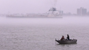 In this file photo, fishermen cast their lines in the Detroit River as the Sam Laud, an iron ore freighter, travels through the fog, Monday, April 11, 2016, in Detroit. (AP Photo/Carlos Osorio)