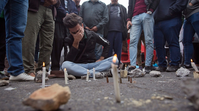 Iraqis gather around a crying man who lit candles by the spot where an Iraqi protester was killed Friday, at Khilani square, in Baghdad, Iraq, Saturday, Dec. 7, 2019. (AP Photo/Nasser Nasser)