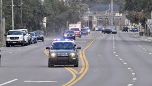 Police cars escort an ambulance after a shooter open fire inside the Pensacola Air Base, Friday, Dec. 6, 2019 in Pensacola, Fla. (Tony Giberson/ Pensacola News Journal via AP)