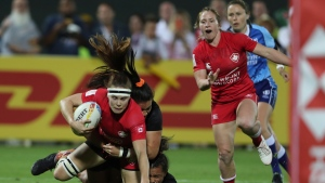 Canada's Karen Paquin is tackled by New Zealand's players in the final match of the Emirates Airline Rugby Sevens in Dubai, United Arab Emirates, Saturday, Dec.7, 2019. (AP Photo/Kamran Jebreili)