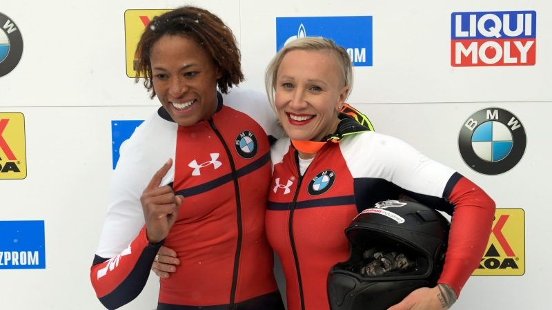 Brakeman, Lauren Gibbs ,left, and Driver Kaillie Humphries,of The United States celebrate their debut winning the women's World Cup bobsled opener in Lake Placid, N.Y., on Saturday, Dec. 7, 2019. (AP Photo/Hans Pennink)