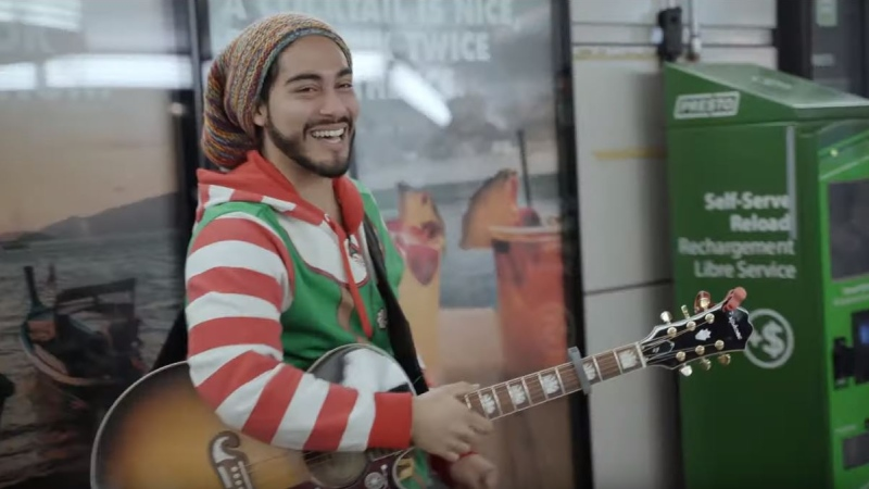 Mo Guzman, 26, from Burlington, a full-time busker for five years, told CTVNews.ca he was 'shocked and surprised' when people starting dropping $20, $50 and $100 dollar notes in his guitar case at King Station in Toronto. (YouTube/KindnessIsContagious)