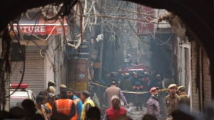 A fire engine stands by the site of a fire in an alleyway, tangled in electrical wire and too narrow for vehicles to access, in New Delhi, India, Sunday, Dec. 8, 2019. (AP Photo/Manish Swarup)