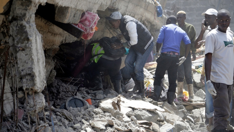 People and rescue workers attend the scene of a building that collapsed in Tasia Embakasi, an east neighbourhood of Nairobi, Kenya on Friday Dec. 6, 2019. (AP Photo/Khalil Senosi)