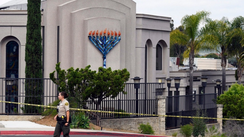 In this Sunday, April 28, 2019 file photo, a San Diego county sheriff's deputy stands in front of the Poway Chabad Synagogue in Poway, Calif. A man who was wounded after an anti-semitic shooter targeted the synagogue in April is suing the synagogue itself, saying the Chabad of Poway failed to use federal funds to institute security measures to protect worshippers. (AP Photo/Denis Poroy, File)