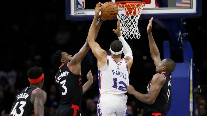 Philadelphia 76ers' Tobias Harris (12) tries to get a shot past Toronto Raptors' Serge Ibaka (9), OG Anunoby (3) and Pascal Siakam (43) during the first half of an NBA basketball game, Sunday, Dec. 8, 2019, in Philadelphia. (AP Photo/Matt Slocum)