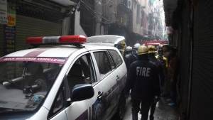 Fire officers gather outside a factory that caught fire in an alleyway in New Delhi, India, Sunday, Dec. 8, 2019. Dozens of people died on Sunday in a devastating fire at a building in a crowded grains market area in central New Delhi, police said. Firefighters fought the blaze from 100 meters (yards) away because it broke out in one of the area's many alleyways, tangled in electrical wire and too narrow for vehicles to access, authorities at the scene said. (AP Photo/Dinesh Joshi)