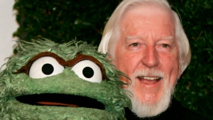 "In this Thursday, April 27, 2006, file photo, Caroll Spinney, right, who portrays ""Sesame Street"" characters Oscar The Grouch, left, and Big Bird, arrives for the Daytime Emmy nominee party at the Hollywood Roosevelt Hotel in Los Angeles. Spinney, who gave Big Bird his warmth and Oscar the Grouch his growl for nearly 50 years on ""Sesame Street,"" died Sunday, Dec. 8, 2019, at the age of 85 at his home in Connecticut, according to the Sesame Workshop. (AP Photo/Reed Saxon, File)"