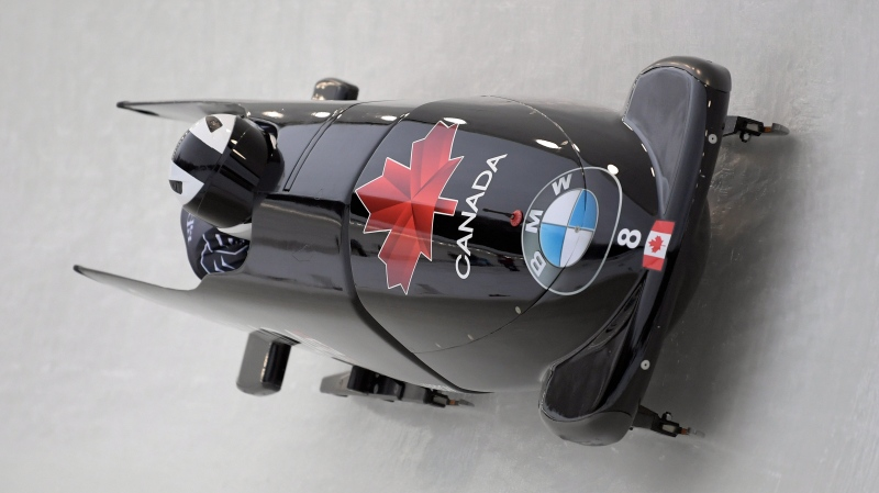 Driver Justin Kripps ,front, and brakeman Cameron Stones, of Canada take a turn during the first run of the men's bobsled World Cup event in Lake Placid, N.Y., on Sunday, Dec. 8, 2019. (AP Photo/Hans Pennink)