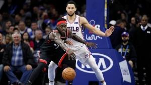 Toronto Raptors' Pascal Siakam, left, chases a loose ball against Philadelphia 76ers' Ben Simmons during the second half of an NBA basketball game, Sunday, Dec. 8, 2019, in Philadelphia. (AP Photo/Matt Slocum)