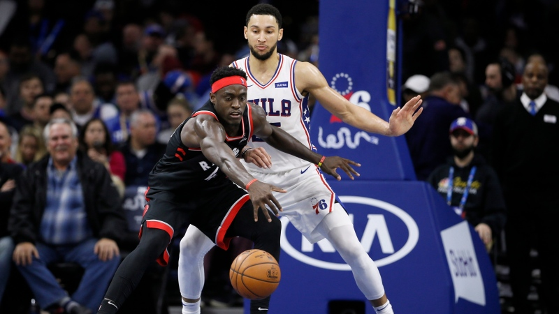 Toronto Raptors' Pascal Siakam, left, chases a loose ball against Philadelphia 76ers' Ben Simmons during the second half of an NBA basketball game, Sunday, Dec. 8, 2019, in Philadelphia. (AP Photo/Matt Slocum)