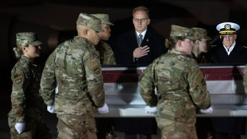 Acting Navy Secretary Thomas Modly, center, and Navy Adm. Michael Gilday, Chief of Naval Operations, look on as an Air Force carry team moves a transfer case containing the remains of Navy Ensign Joshua Watson on Sunday, Dec. 8, 2019, at Dover Air Force Base, Del. (AP Photo/Cliff Owen)