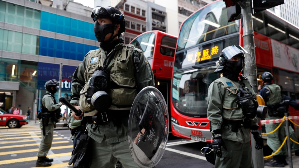 Police guard in front of a bus stop Monday, Dec. 9, 2019, in Hong Kong, the morning after hundreds of thousands of demonstrators crammed into Hong Kong's streets. (AP Photo/Vincent Thian)