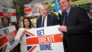 Home Secretary Priti Patel, center left, Britain's Prime Minister Boris Johnson, center, and MP Will Quince pose holding a sign before a rally event as part of the General Election campaign, in Colchester, England, Monday, Dec. 2, 2019.Hannah McKay/Pool Photo via AP)