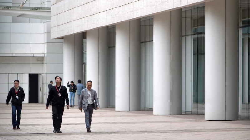 Employees walk through Huawei's campus in Shenzhen in southern China's Guandong Province, Thursday, Dec. 5, 2019.