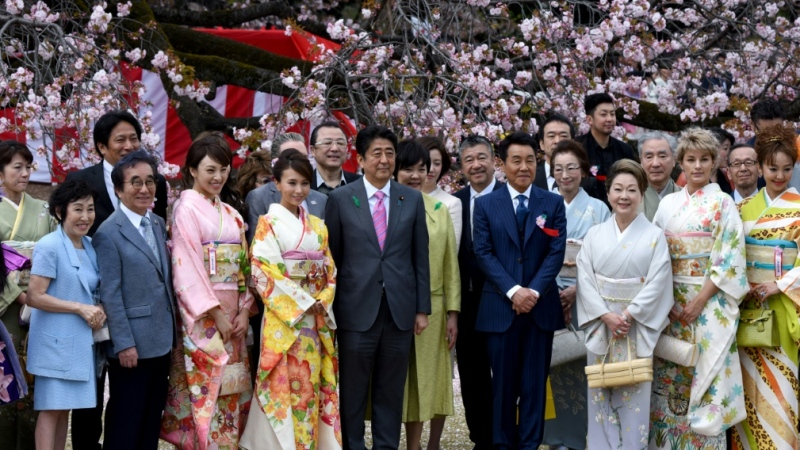 Japanese Prime Minister Shinzo Abe (C), pictured here at 2015's cherry blossom party, has already weathered two cronyism scandals in recent years. (AFP)
