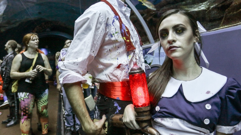 "In this Saturday, Sept. 5, 2015, photo, a woman dressed as Little Sister, a character from the popular ""BioShock"" video game, attends a private party held at the Georgia Aquarium as part of Dragon Con in Atlanta. (Ron Harris / AP Photo)"