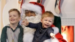 Two boys sit for a photo with Santa. (AP Photo/Elaine Thompson)