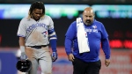 Toronto Blue Jays' Vladimir Guerrero Jr., left, walks with assistant athletic trainer Jose Ministral to the dugout after suffering an injury while reaching second base during the ninth inning of the team's baseball game against the Baltimore Orioles, Wednesday, Sept. 18, 2019, in Baltimore. (AP Photo/Julio Cortez)