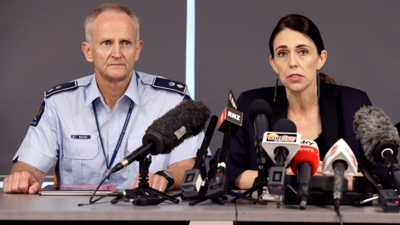 New Zealand Prime Minister Jacinda Ardern addresses a press conference as police Superintendent Bruce Bird, left, watches in Whakatane, New Zealand, Tuesday, Dec. 10, 2019. (AP Photo/Mark Baker)