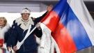 In this Feb. 7, 2014 file photo Alexander Zubkov of Russia carries the national flag as he leads the team during the opening ceremony of the 2014 Winter Olympics in Sochi, Russia. (AP / Mark Humphrey, file)