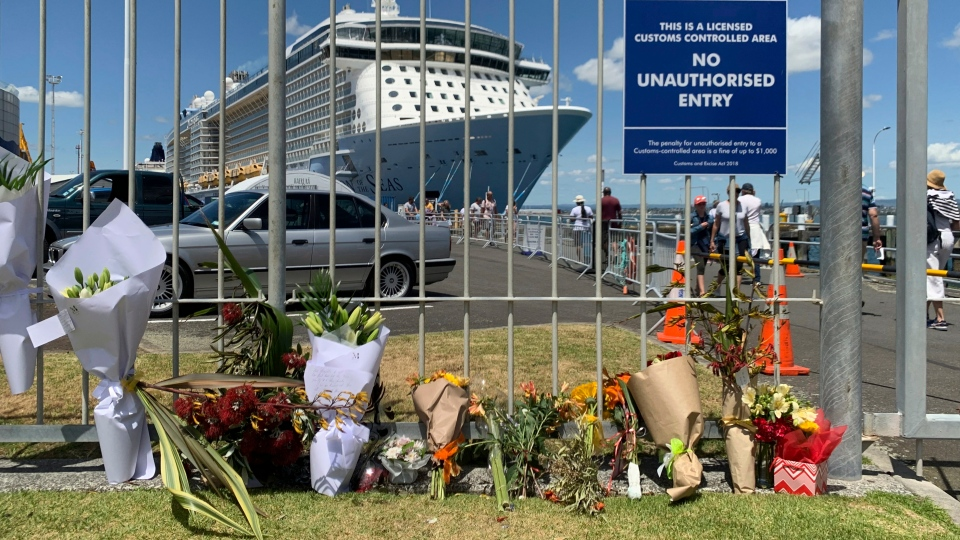 Flowers are laid on makeshift memorial is seen in front of cruise ship Ovation of the Seas, in Tauranga, New Zealand, Tuesday, Dec. 10, 2019. (AP Photo/Nick Perry)