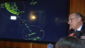 In this image made from video, Gen. Eduardo Mosqueira, right, of the Fourth Air Brigade speaks to the media next to a map of the area where the airplane is missing, in Punta Arenas, Chile, Monday, Dec. 9, 2019. (AP Photo)