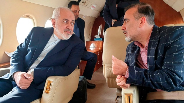 In this photo released on twitter account of Iran's Foreign Minister Mohammad Javad Zarif, left, speaks with Iranian scientist Massoud Soleimani onboard a plane while leaving Zurich, Switzerland for Tehran, Iran, Saturday, Dec. 7, 2019. (Javad Zarif twitter account via AP)